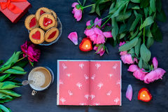 Love and care concept. Romantic style composition - opened notebook surrounded with peonies, cookies, mug with coffee, candles, pr. Esent box on the black wooden Stock Photo