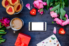 Love and care concept. Romantic style composition - smart phone surrounded with peonies, cookies and mug with coffee, candles, pre. Sent box on the black wooden Royalty Free Stock Images