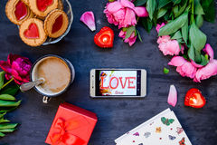 Love and care concept. Romantic style composition - smartphone with LOVE word surrounded with peonies, cookies and mug with coffee. Candles, present box on the Stock Photography