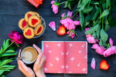 Love and care concept. Romantic style - Female hands holding coffee mug and opened notebook surrounded with peonies, cookies, cand. Les on the black wooden Stock Images