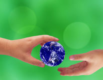 Love and Care The Earth Concept. Hand and blue planet on green blur background, Elements of this Image Furnished by NASA Stock Photo