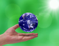 Love and Care The Earth Concept. Hand and blue planet on green blur background, Elements of this Image Furnished by NASA Royalty Free Stock Image