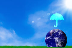 Love and Care The Earth Concept. Umbrella icon and blue planet on blue sky background, Elements of this Image Furnished by NASA Stock Photo