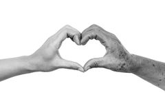 Love and care elderly people. Hands of the female elderly and a young woman forming a heart shape together / Love and care elderly people concept Stock Images