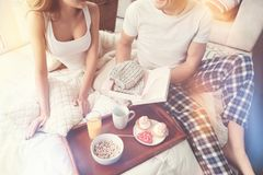 Gallant nice guy giving a present. Love and care. Romantic emotional caring men making a lovely surprise for his girlfriend while they having a breakfast and Stock Photography