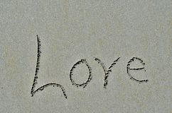 Love carved into ocean beach sand. Stock Photography