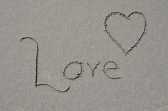 Love carved into ocean beach sand. Royalty Free Stock Photo