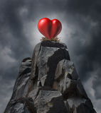 Love Challenge. Love and relationship challenge problem concept and romantic life trouble or heartache and loneliness as a red heart  sitting high on cliff in a Royalty Free Stock Photo
