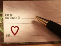 Love Check. A check with a red heart on the memo line and a pen Stock Photography