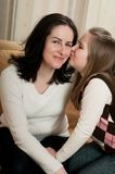 Love - child kissing mother. Child (cute ligirl) kissing her mother - indoors at home Stock Photography