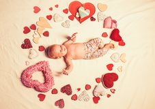 Love. Childhood happiness.Valentines day. Small girl among red hearts. Sweet little baby. New life and birth. Family stock photography