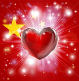 Love China flag heart background. Flag of China patriotic background with pyrotechnic or light burst and love heart in the centre Royalty Free Stock Photo