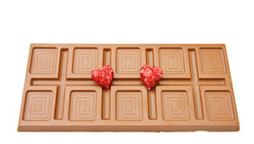 Love and chocolate. Large bar of fine Belgian chocolate with red hearts for the celebration of a special day. Isolated on white background stock photos