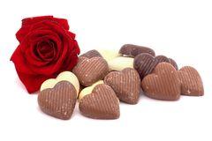 Love chocolates. A rose and heart-shaped chocolates on white Royalty Free Stock Photos