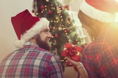 Love at Christmas. Beautiful young couple in love sitting on a living room floor next to a nicely decorated Christmas tree and exchanging presents Royalty Free Stock Images