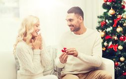Man giving woman engagement ring for christmas. Love, christmas, couple, proposal and people concept - happy men giving engagement ring in little red box to Royalty Free Stock Photos