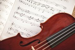In love with classic music. Close up view of brown violin lying on music score sheet. Violin lessons. In love with classic music. Close up view of brown violin stock image