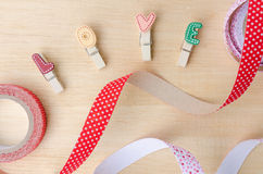 Love clips with cute ribbons on wooden background Royalty Free Stock Photos