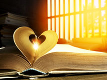LOVE. Close up the heart shape of open old book page and sparkle middle with orange light side in the morning. Selective focus and copy space Royalty Free Stock Photography