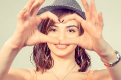 Woman making heart sign, symbol with hands. Love. Closeup portrait smiling happy young woman making heart sign, symbol with hands isolated yellow wall royalty free stock photo