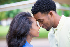 In love. Closeup portrait of a young couple, guy in yellow shirt looking into woman's eyes with blue shirt, head to head, happy moments, positive human emotions Royalty Free Stock Images