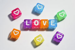Love. Closeup of small brightly colored beads Royalty Free Stock Images