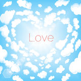 Love in the clouds. In the blue sky with the sun glare Stock Image