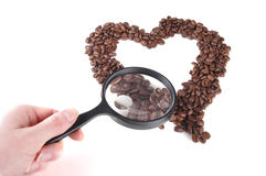 Love of Coffee 2. A heart made from coffee beans. Some of the coffee beans are under a magnifying glass. White background Stock Images