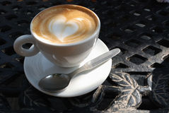 Love Coffee. Alfresco cup of coffee, the froth has swirled into a heart shape Stock Photography