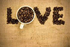 Love coffee. Coffee beans and mug used to spell love on hessian sack Stock Image