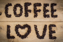 Love coffee beans on grain wood Royalty Free Stock Photo