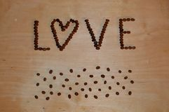 Love is coffee beans. Spilled coffee grains and love title effect on wooden surface. Soft dirty background Royalty Free Stock Images