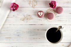 Love and coffee for breakfast. Coffee with flowers, macaroons and love on a white wooden background stock photo