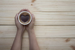 Love coffee cup with Heart shape in hand on table Royalty Free Stock Photography