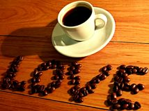 Love Coffee. Espresso cup with sign Love made from coffee beans Royalty Free Stock Photography