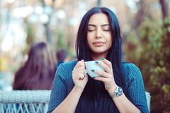 Love for coffee. Portrait of cute girl drinking enjoying her tea on the balcony over outside terrace with green bush background, w. Earing blue grey blouse and stock image