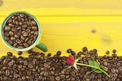 We love coffee. Roses resting on the coffee. Coffee beans, poured out on Yellow wooden table. Stock Photography