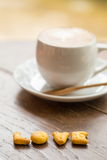 Love coffee on wooden table. Love hot Cup of Coffee on a Wooden Table Stock Image
