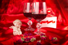 A love composition. Composition with two glasses of wine, angel figurines, and gift boxes on red blurred background Royalty Free Stock Image