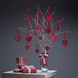 Love composition. Tree with red hearts in glass vase and red gifts on white table over gray background Royalty Free Stock Photo