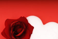 Love concept. With rose and white heart on red background Royalty Free Stock Images