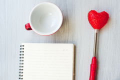 Love concept, blank coffee up, heart shape. And paper notebook on gray floor Royalty Free Stock Photography