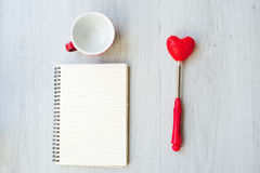 Love concept, blank coffee up, heart shape. And paper notebook on gray floor Royalty Free Stock Image