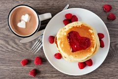 Love concept breakfast pancakes, hot chocolate and raspberries over wood. Pancakes with jam in shape of heart, hot chocolate and raspberries over a wood Stock Image