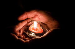 Love concept with candle. Burning candle with heart shape in hands Royalty Free Stock Photography