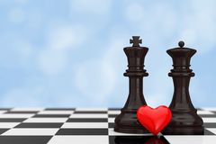 Love Concept. Chess King and Queen Figures with Red Heart over C. Hessboard on a blue background. 3d Rendering Royalty Free Stock Photo