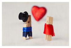 Love concept. Clothespins: romantic couple. Wedding. Valentines day. Man, woman. Gentleman in black hat, woman in red dress. Red heart background. (Soft focus Royalty Free Stock Photography