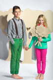 Love concept. Couple of kids. boy gives a girl cardboard flowers Stock Photos