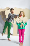 Love concept. Couple of kids. boy gives a girl cardboard flowers Royalty Free Stock Image