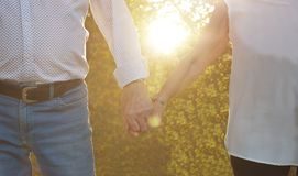 LOVE CONCEPT. ELDERLY COUPLE HOLDING HANDS ON SUNSET. CLOSE-UP stock photo